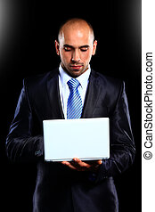 Business man with a laptop -over a black background