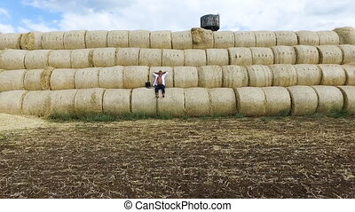 Business man with a laptop resting on straw bales. Flying drone. Ecology. Natural product. Series.