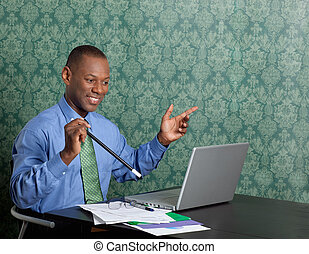 Business man with a magical wand in front of laptop at desk