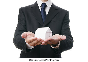 Business man with a paper house in the hands
