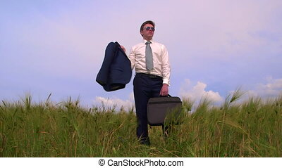 Business man with bag standing in a field