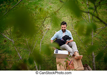 Business man with dog and laptop working outdoors in garden, home office concept.