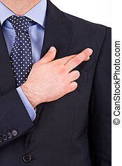 Business man with fingers crossed.