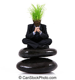 man with grass head sitting on a rock