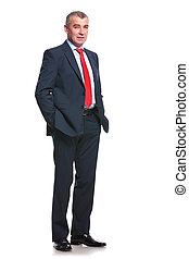 full length picture of a mid aged business man holding his hands in his pockets and looking into the camera. isolated on a white background