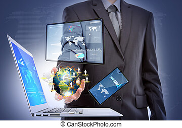 Business man with laptop, mobile phone, touch screen device (Elements of this image furnished by NASA)