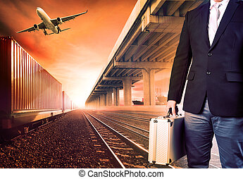business man with metal breifcase investment standing against airpalne ,trains and ship port transport and logistic background
