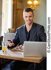 Business man With Mobilephone And Laptop In Restaurant