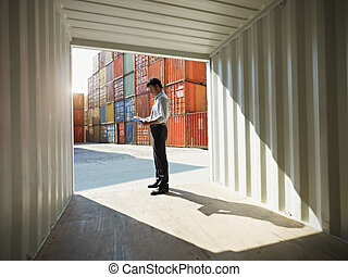 business man with shipping containers - portrait of mid ...