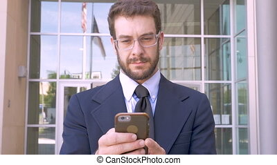 Business man with smart phone app technology and smiling outside office building