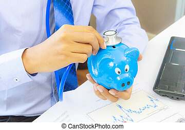 business man with stethoscope checking piggy bank ,...