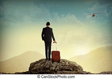 Business man with suitcase on the top of the mountain