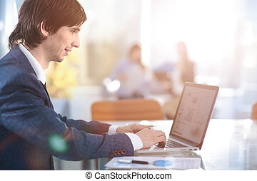 Business man working at office with laptop, tablet and graph data documents