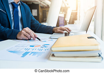 Business man working at office with laptop and documents on his desk. Analyze plans, papers, hands keyboard