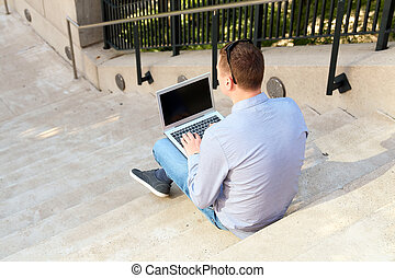 business man working with a laptop, sitting outside