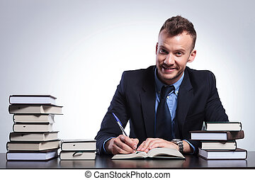 business man writes and smiles