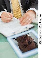 Business man writing on a notepad
