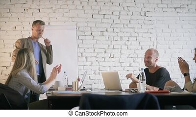 Business manager is suggesting an idea to his colleagues and they accept it. Creative business team applauses their boss, smiling and discussing ideas in office