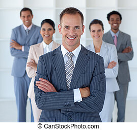 Smiling business manager standing in office leading his team
