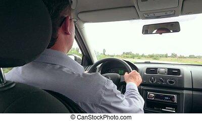 Business man's hands driving a modern car - Close up of...
