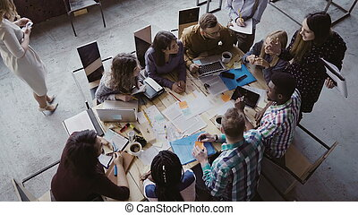 Business meeting at loft shared coworking space. Multiethnic team talking, woman manager giving direction to group of young people. Brainstorming at start-up company. Top view.