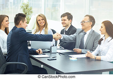 Business meeting at the table and handshake of business partners in a modern office