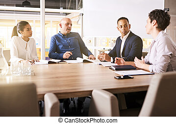 Business meeting between four high power, racially diverse, eclectic individuals