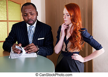 Business meeting between red head woman and black man