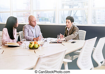 Business meeting between three professional partners early in the morning