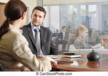Business man and woman talking in the office - other people in the background