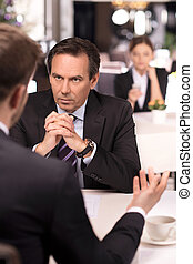 Business meeting. Business people in formalwear discussing something while sitting at the restaurant