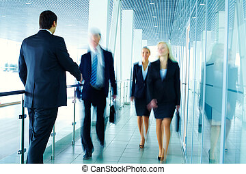 Business people meeting each other in the office corridor and shaking hands