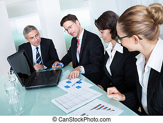 Group of diverse business executives holding a meeting around a table discussing graphs showing statistical analysis