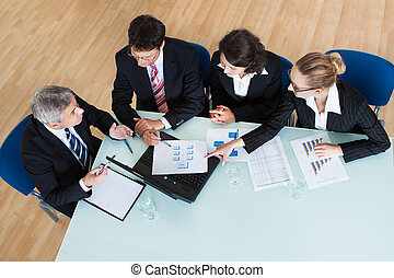 Overhead view of a group of diverse business executives holding a meeting around a table discussing graphs showing statistical analysis