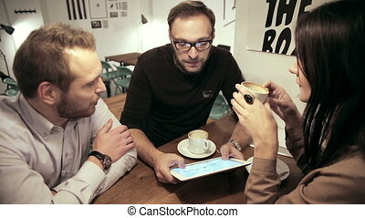 Business meeting in cafe. team is using the tablet