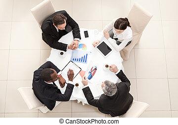 Business meeting in restaurant - Team sitting behind desk, ...
