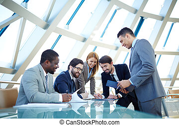 Business meeting - Group of business people discussing data...