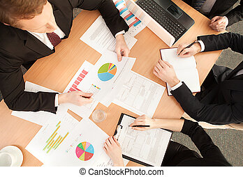 Business meeting. Top view of business people in formalwear sitting at the table and discussing something