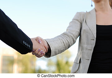Business men and women shaking hands on a light background. Meeting.