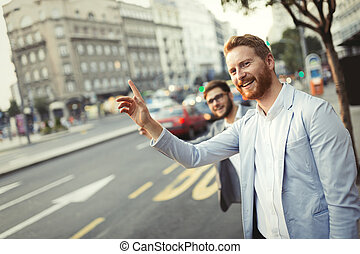Business men hailing a cab in busy city