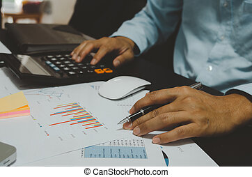 Business men hold pen and calculator to see graphs and report sales and business growth.Business document finance and statistics of profit in management.