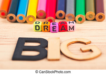 business motivational and inspirational quotes, colorful cubes with words DREAM BIG on wooden desk