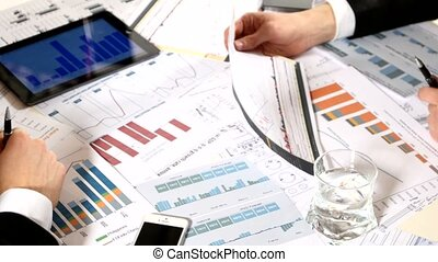 Business negotiations: a tablet with graphs on the table. discussion developing a business project and analyzing market data information