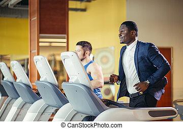 African businessman on a treadmill.