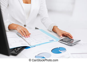 business, office, tax, school and education concept - woman hand with calculator and papers