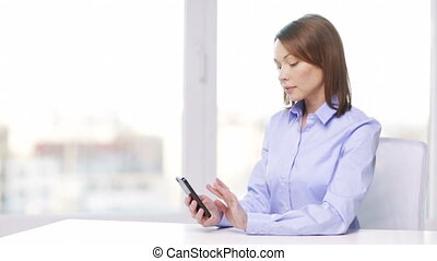 busy businesswoman with smartphone in office