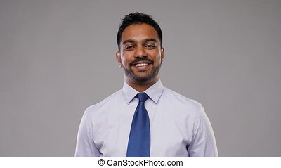 indian businessman in shirt with tie over grey - business,...
