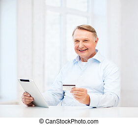 old man with tablet pc and credit card at home - business,...
