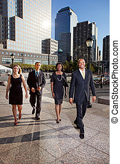 A group of business people walking down town in a large city