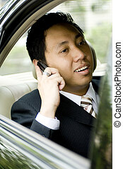 A young business executive making a phone call in the back seat of a car